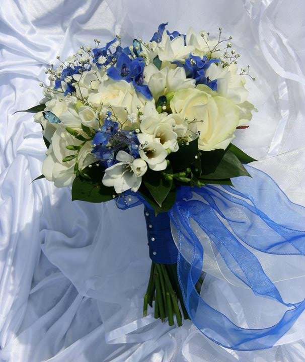 Royal blue and white bride bouquet using delphinium, freesia and roses