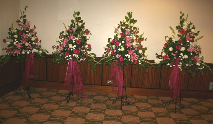 Pedestal arrangements for wedding in hot pinks and ivory