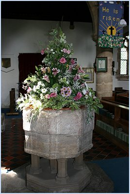 Wedding church flowers on a font