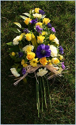 Yellow and Blue Spray wreath using roses, carnations, freesia and daisy chrysanths