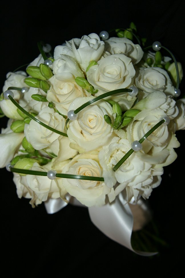 Contemporary bridal bouquet of white roses and freesia overlayed with pearl strands