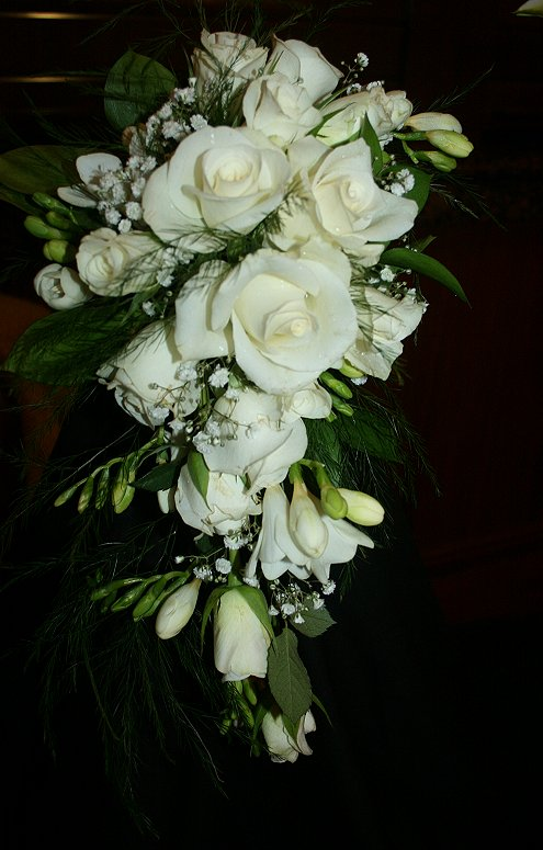 White bridal shower bouquet using roses, freesia and gyp