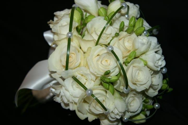 Bridal bouquet, ivory roses and freesia with looped beargrass threaded with pearl heads.