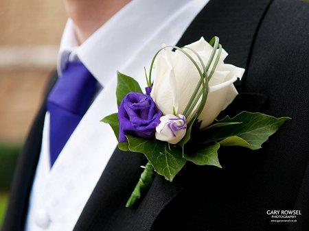 Ivory rose, purple lizianthus, bear grass loops, buttonhole