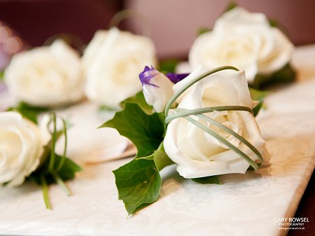Ivory rose buttonhole with beargrass overlay