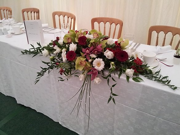 Wedding top table arrangement with orchids and roses