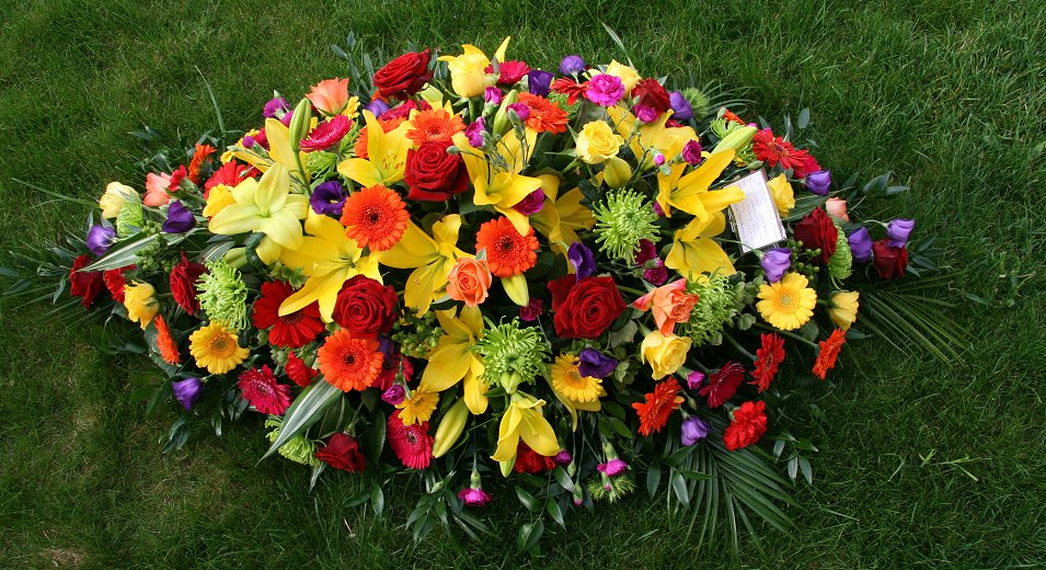Jewel coloured sympathy tribute coffin spray using bright colours